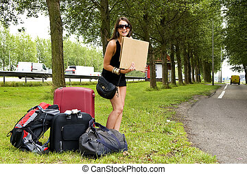 Hitch hiker - Young, smiling, woman, with a lot of luggage,...