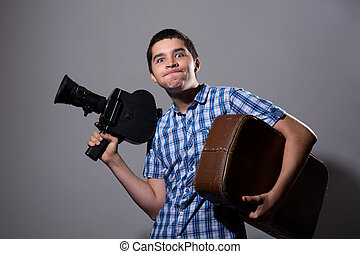 Portrait of a young cameraman with old movie camera and a...