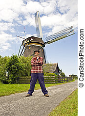 Miller - Sturdy miller in front of a classic Dutch Windmill