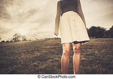 Young woman wearing skirt standing in park at sunset - A...