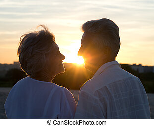 Elderly couple in love at sunset on a summer evening