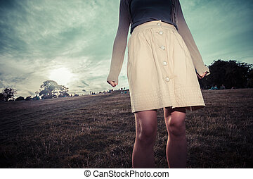 The skirt of a woman blowing in the wind at sunset - A young...