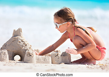 Little girl playing at beach - Little girl at tropical beach...