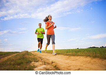 Couple running at sunset - Cross-country trail running...