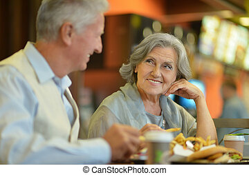 Mature couple eating french fries - Beautiful mature couple...