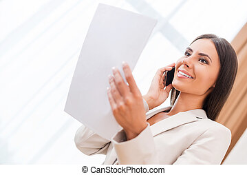 Happy with a contract signed. Low angle view of happy young businesswoman in suit talking on the mobile phone and holding document