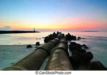 Sunrise at the beach near a lighthouse