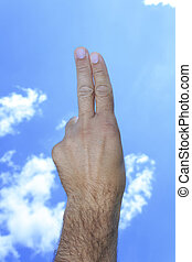 Hand showing two fingers in sky clouds background