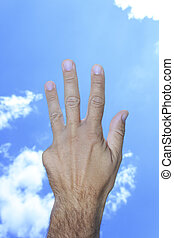 Hand showing four fingers in sky clouds background