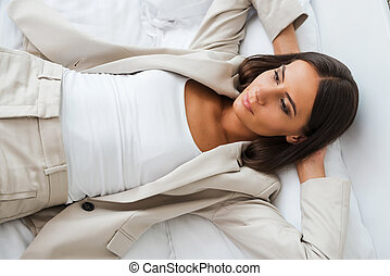 Tired after hard working day. Top view of beautiful young businesswoman in suit holding hands behind head and keeping eyes closed while lying in bed at the hotel room
