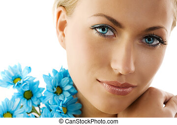 blue eyes and blue daisy - close up of a cute woman with big...