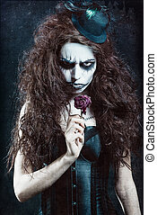 Woman in image of gothic freak clown with withered flower....