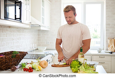 Handsome man cooking at home preparing salad in kitchen -...