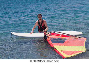 Mature adult windsurfing - Male adult windsurfer standing in...