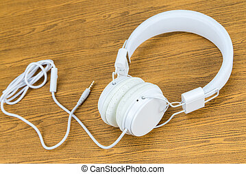 White headphone on woode background