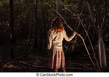Young woman standing in a clearing of the forest - A young...
