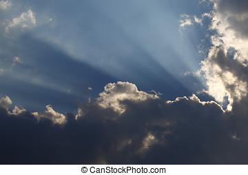 Sun rays through storm clouds on a blue sky