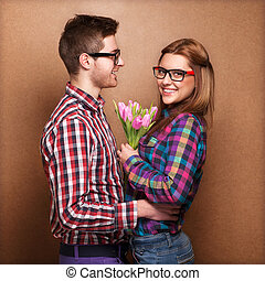 Beautiful young couple hug each other, the girl holding a bouque