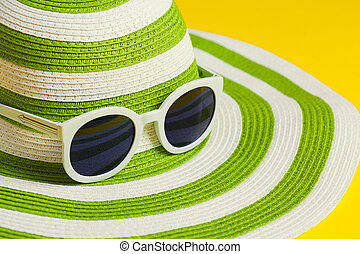 Pretty green hat with sunglasses on yellow background