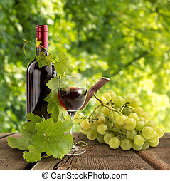 red wine, vine leaves and grape on wooden table