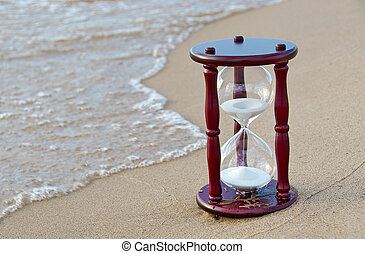 sand timer in sand - Sand timer in beach sand at the...