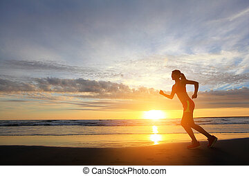 Running - young woman running on the beach at sunrise, asian