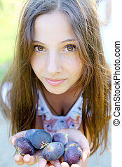 Young beautiful woman with figs in hands