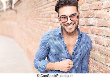 man with glasses looks to side and laughs - happy youn man...