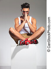 man sitting on a cube is praying in studio