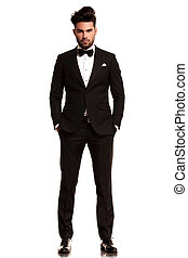 man wearing tuxedo standing with hands in pockets - fashion...