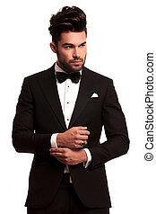 fashion elegant man in tuxedo fixing his sleeve on white...