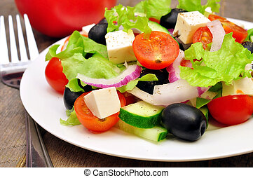 Greek salad and fork on a wooden table