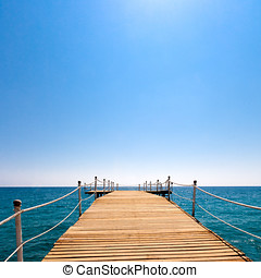 Pier in the sea and blue sky. Vacantion and relaxion. Coast....