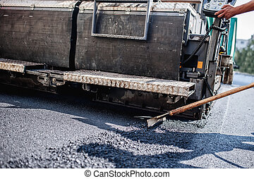 Male worker operating asphalt paver machinery on...
