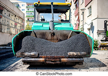 industrial paver laying fresh asphalt and bitumen pavement...