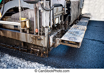 pavement machine laying fresh asphalt or bitumen on top of...