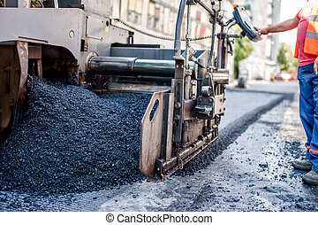 worker or engineer operating an paving machine - worker or...