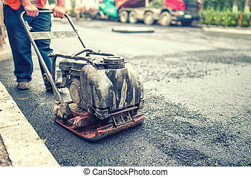 asphalt worker at road repairing and construction site with...