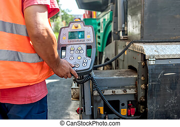 close up of worker hand operating asphalt paver machinery on...