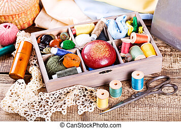 various threads and sewing tools in box on wooden background