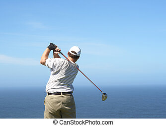Golfer on the tee box - Young male golfer hitting the ball...