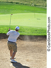 Golfer in the sand bunker - Young male golfer hitting the...