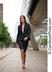 Attractive business woman walking downtown - Portrait of an...