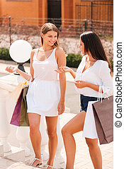Discussing their day shopping. Two beautiful young women with shopping bags walking together and talking