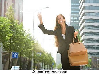 Businesswoman raising arm for taxi in the city