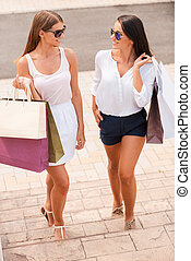 Relaxing after day shopping. Top view of two beautiful young women with shopping bags walking together and talking