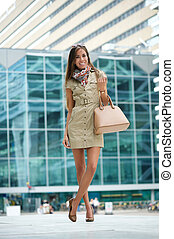 Young woman posing in the city with handbag