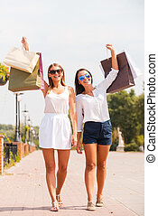 Feeling happy after day shopping. Full length of two beautiful young women showing their shopping bags and smiling while walking by the street together