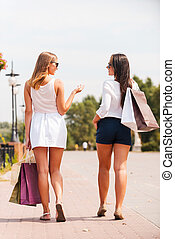 After the day shopping. Rear view of two beautiful young women with shopping bags walking by the street and talking