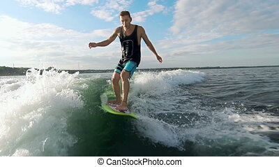 Wave Lord - Man surfing on waves and crouching on surfboard